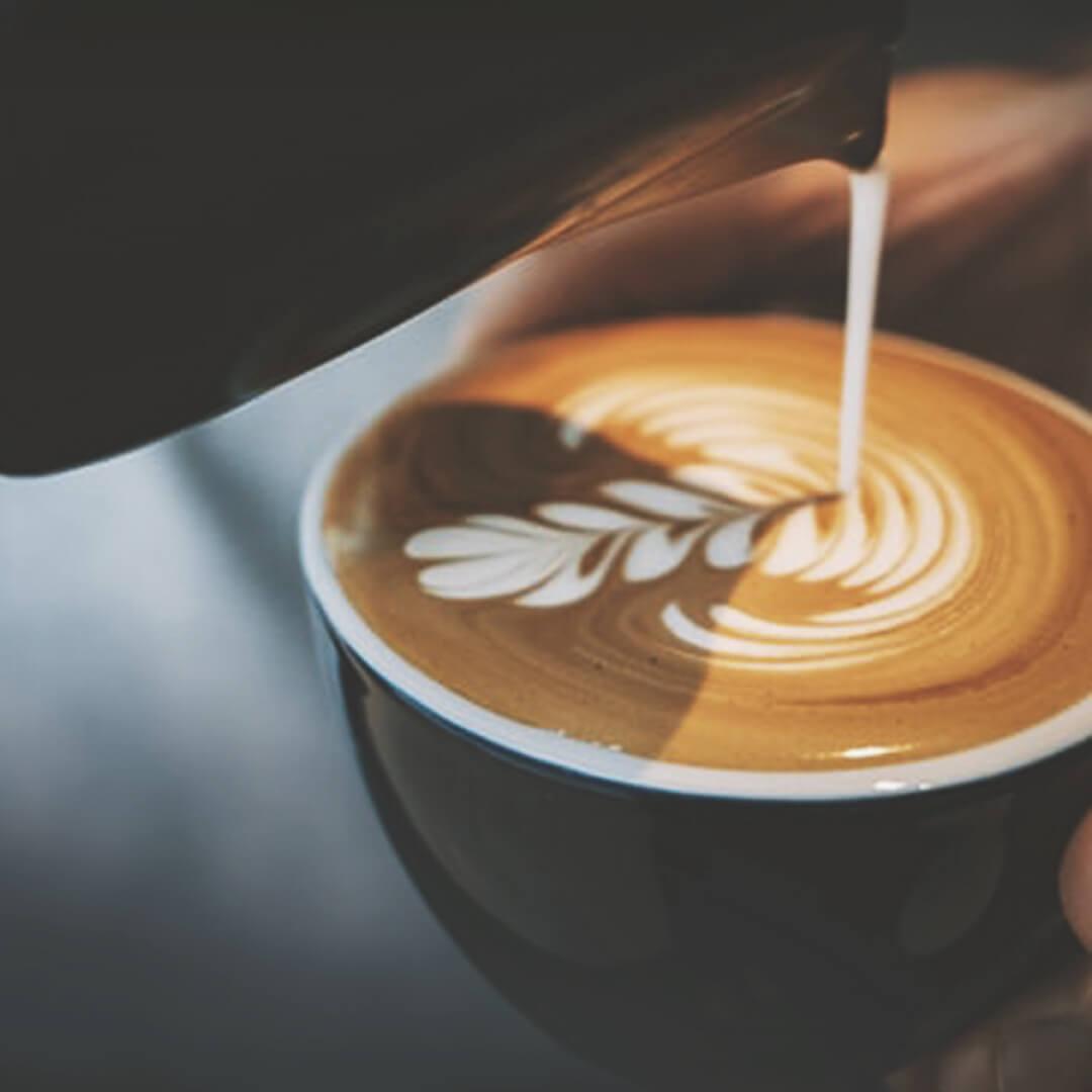 Latte Art wird in Cappuccino gegossen