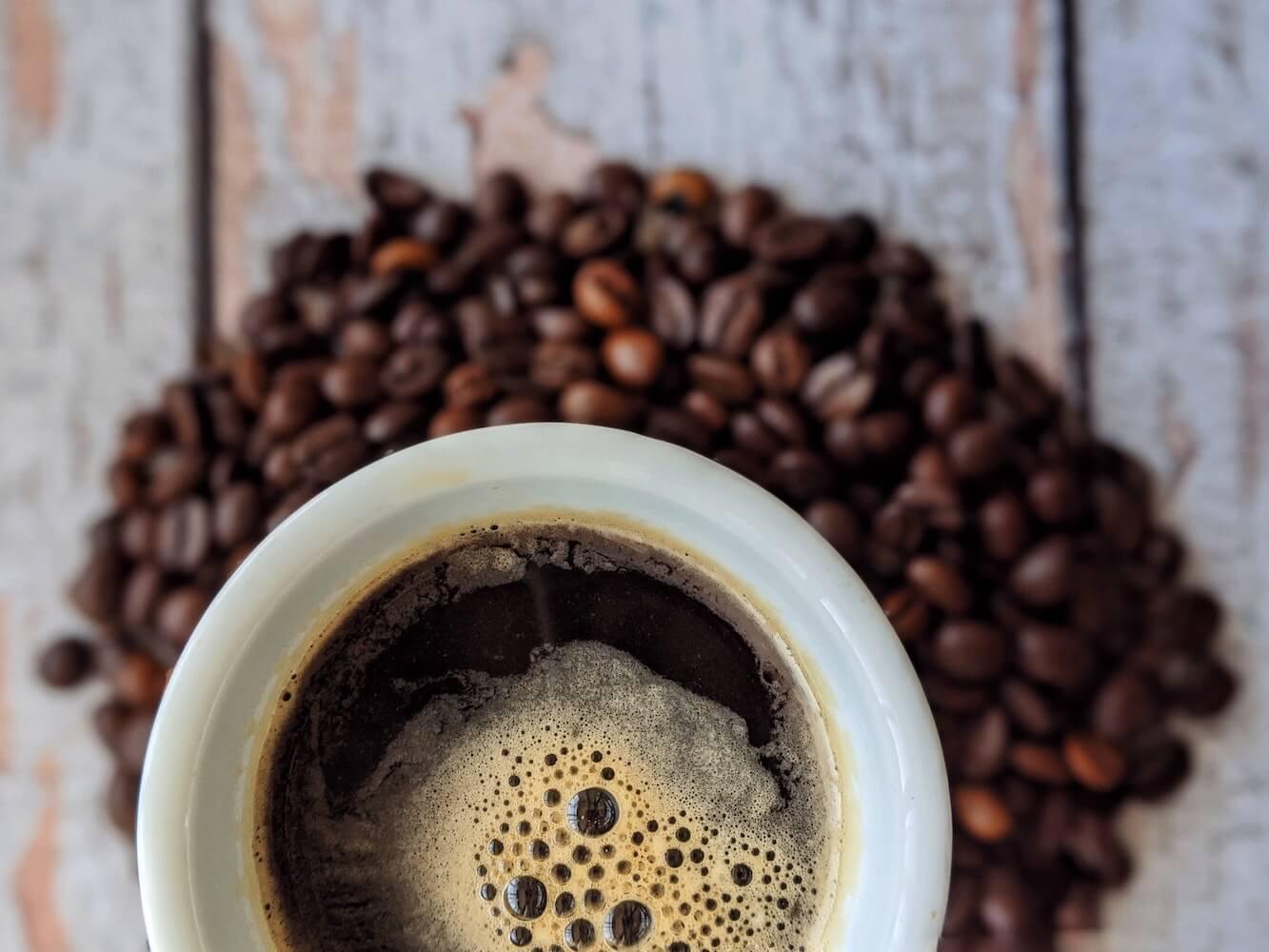 frischer Kaffee in Tasse mit Kaffeebohnen auf Tisch