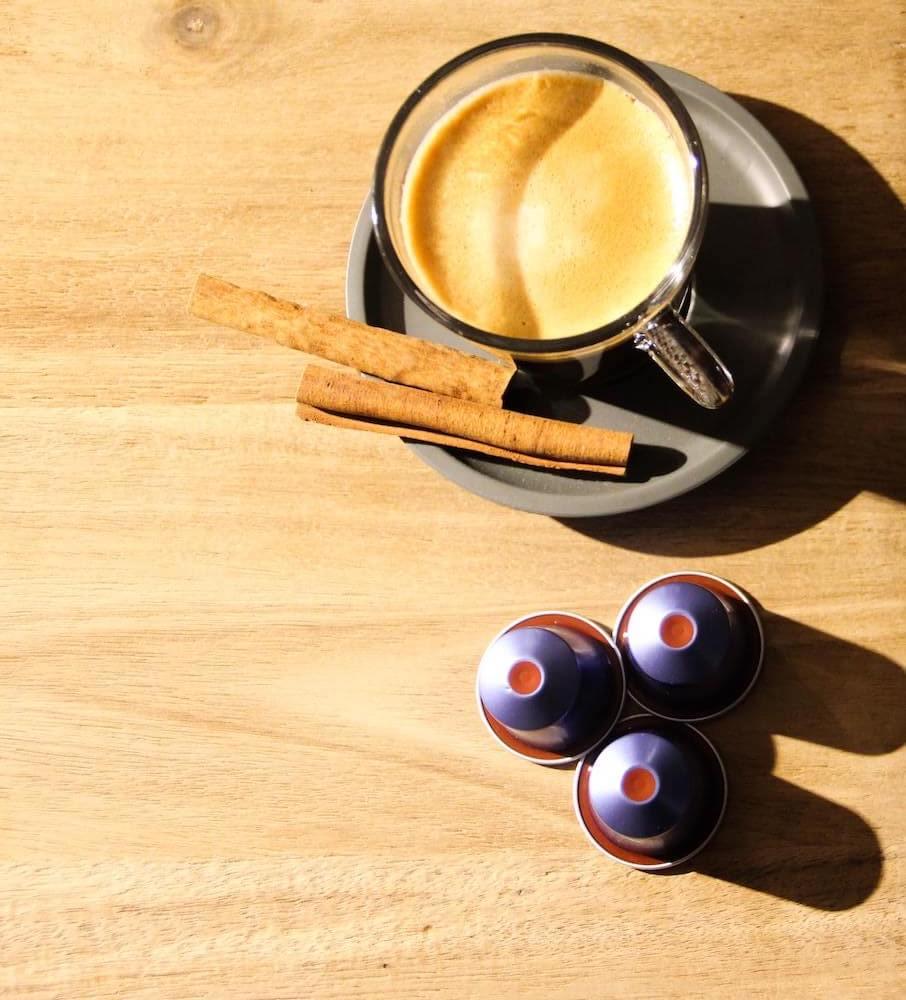 Gourmesso Kapseln mit Kaffee in Tasse auf Tisch