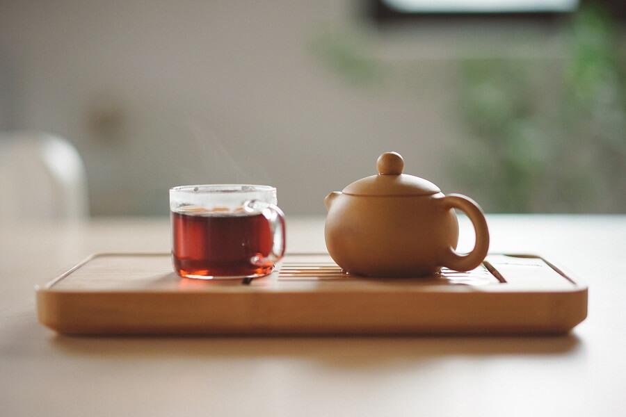 Teetasse mit Teekanne auf Holztablett