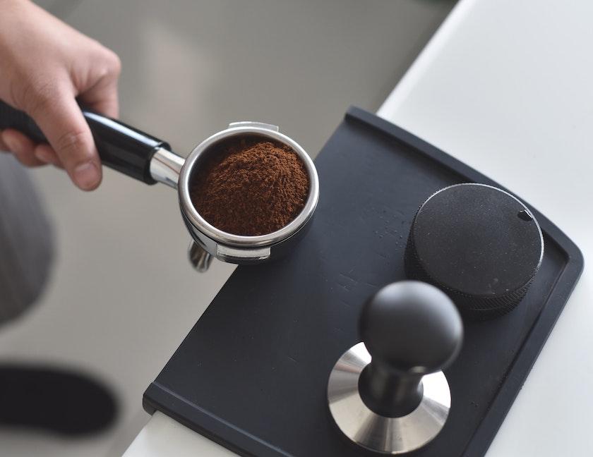 frisch gemahlenes Kaffeemehl auf Tamperstation