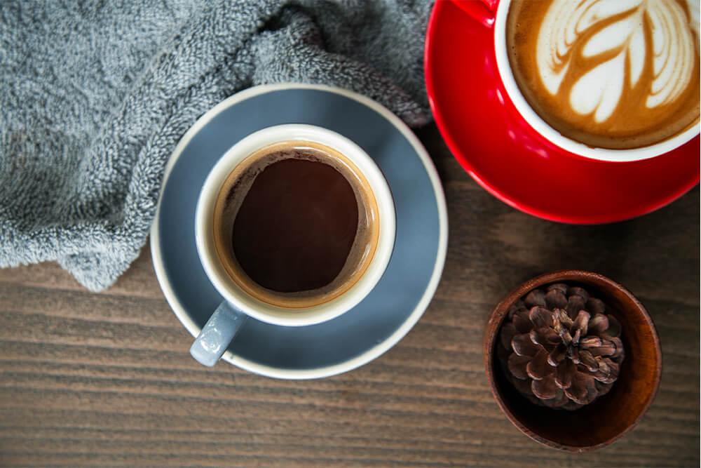 Kaffeetassen auf Holztisch mit Kuscheldecke