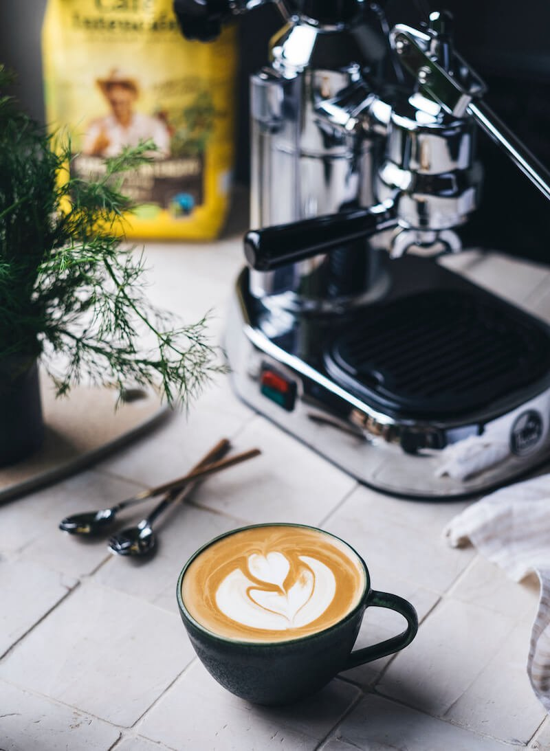 Café Intención Kaffee neben Siebträgermaschine und Cappuccino