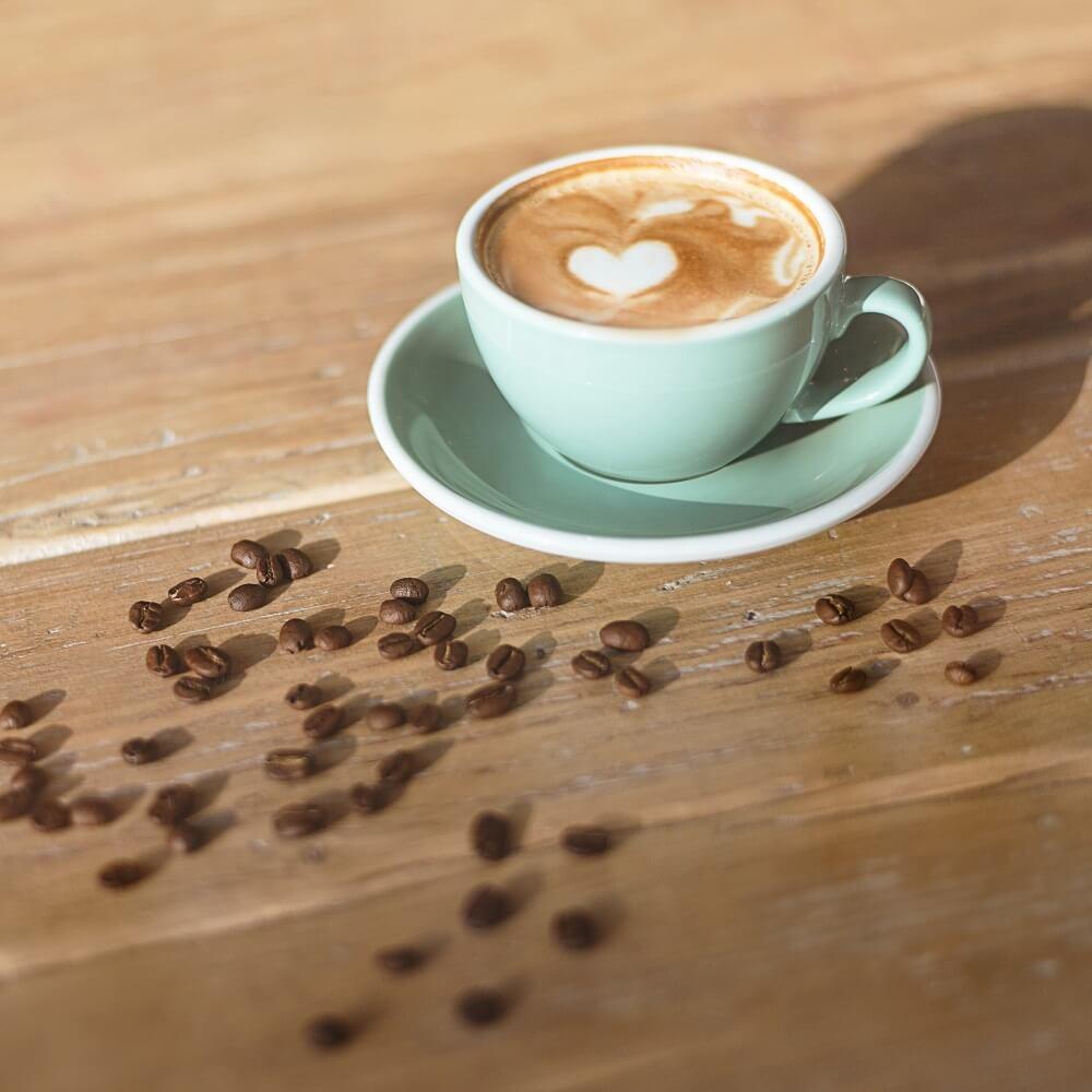Cappuccino und Kaffeebohnen auf Holztisch