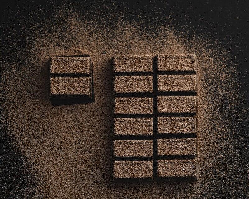 Eine Tafel Schokolade mit Kakaopulver bestreut
