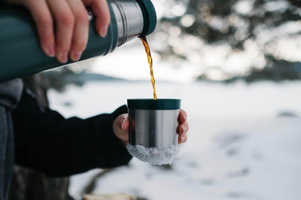 Thermoskanne Kaffee eingießen in Tasse
