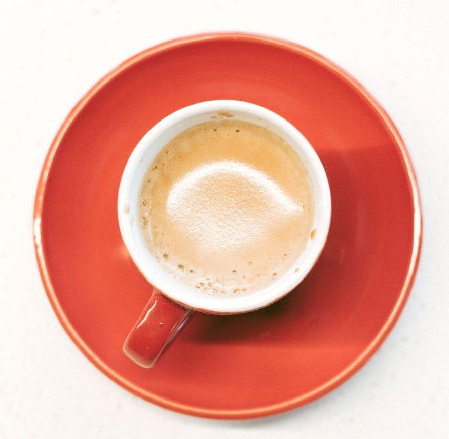 Käfer Kaffee in roter Tasse