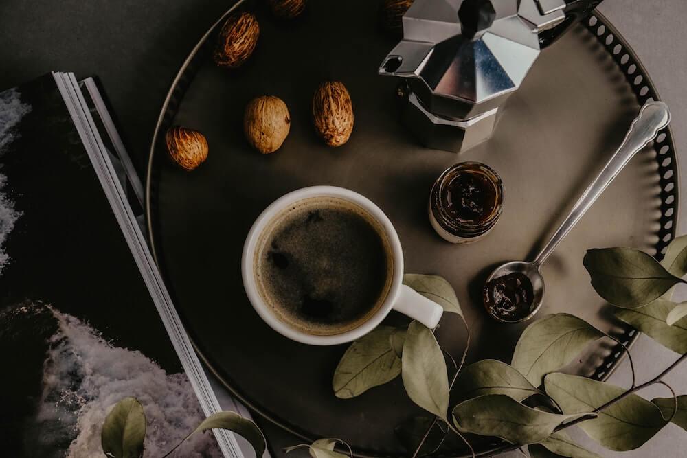 Frischer Kaffee neben Muskatnüssen und Pflanze