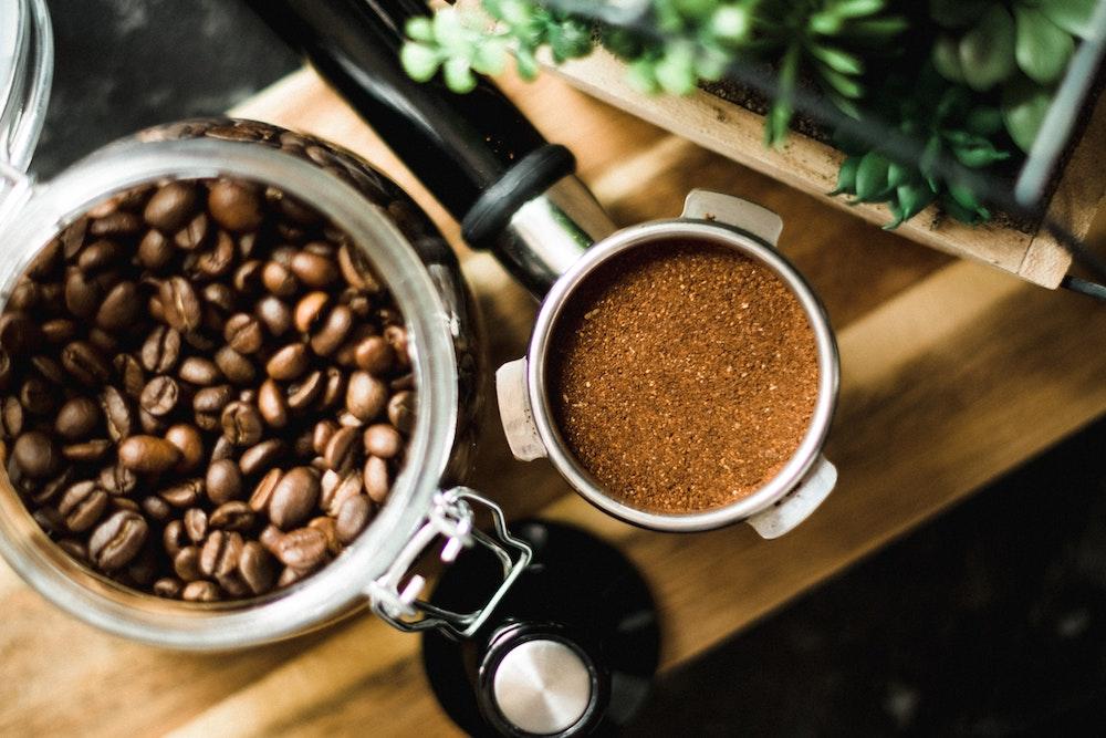 Kaffebohnen im Glas und Topfpflanze