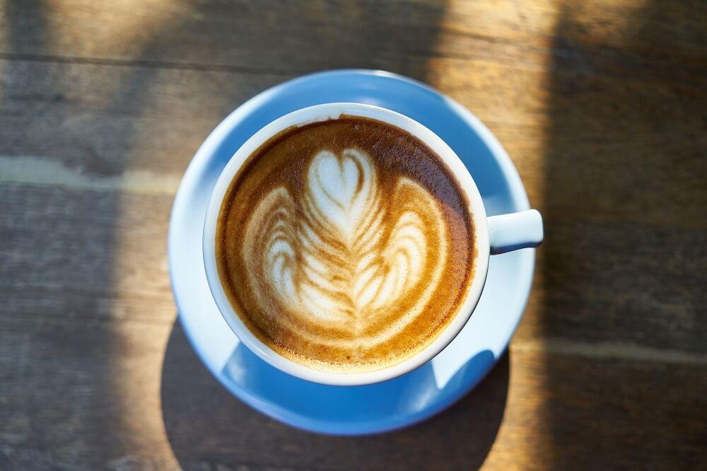 Cappuccino mit Latte Art in blauer Tasse