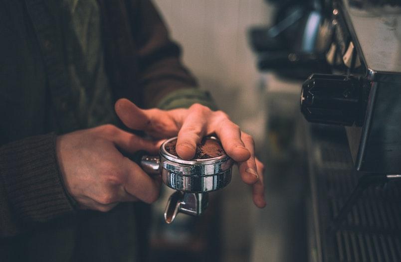 Kaffeemehl wird im Siebträgerhalter angedrückt
