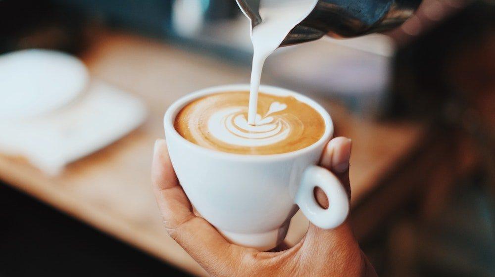 Milchschaum-wird-in-Cappuccino-gegossen