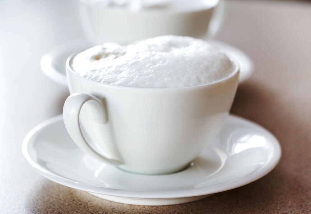 Milchschaum in weißer Tasse