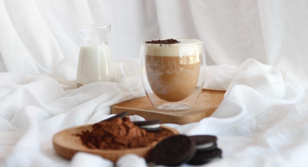 Cappuccino im Glas mit Kaffee Zusätzen Milch und Sirup im Kaffee