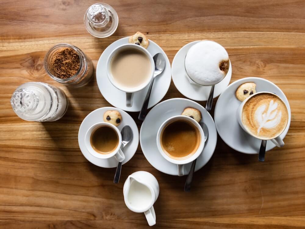 Milchkaffee, schwarzer Kaffee, Latte Macchiato, Cappuccino und Milch auf Holztisch