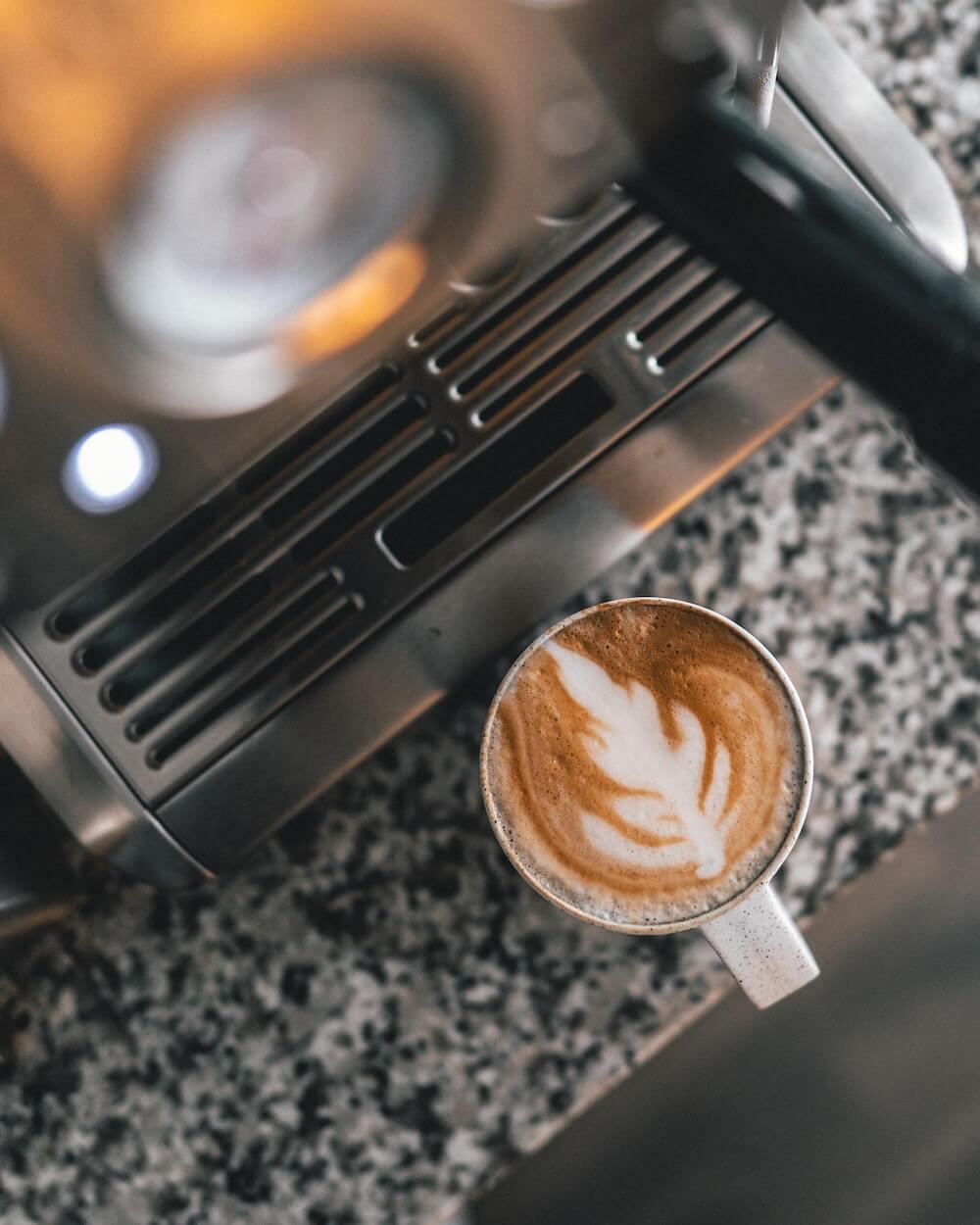 Frischer Kaffee neben einer Kaffeemaschine