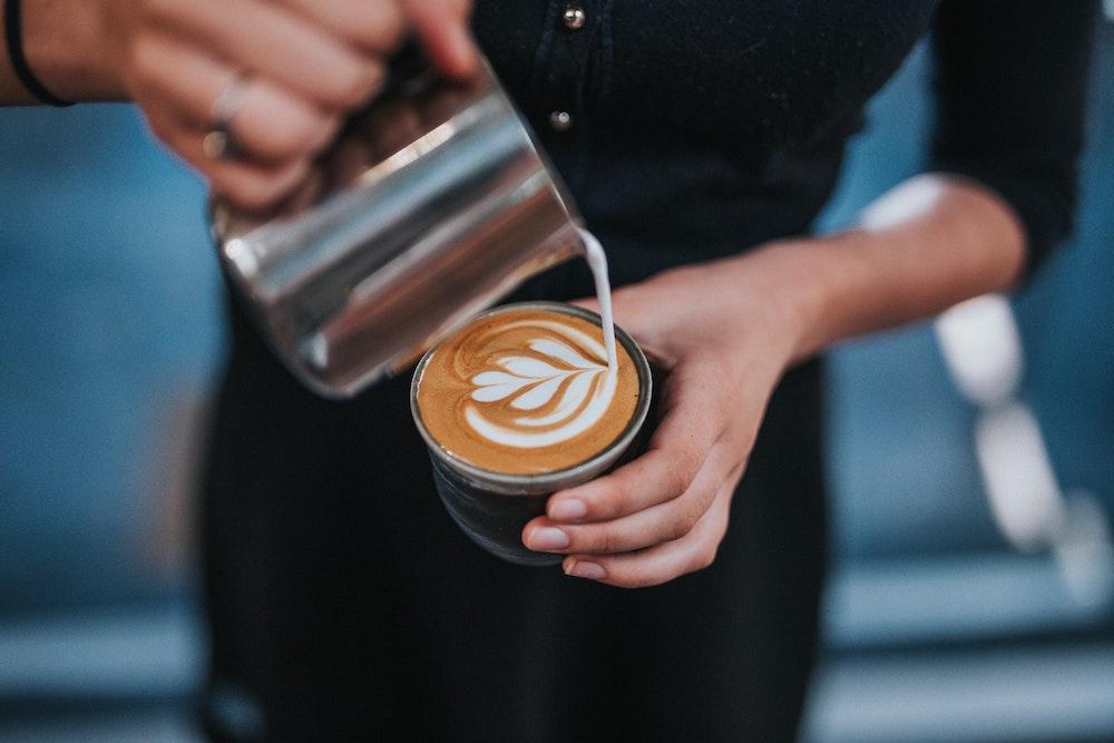Latte Art Herz wird mit Milch in Kaffee gegossen