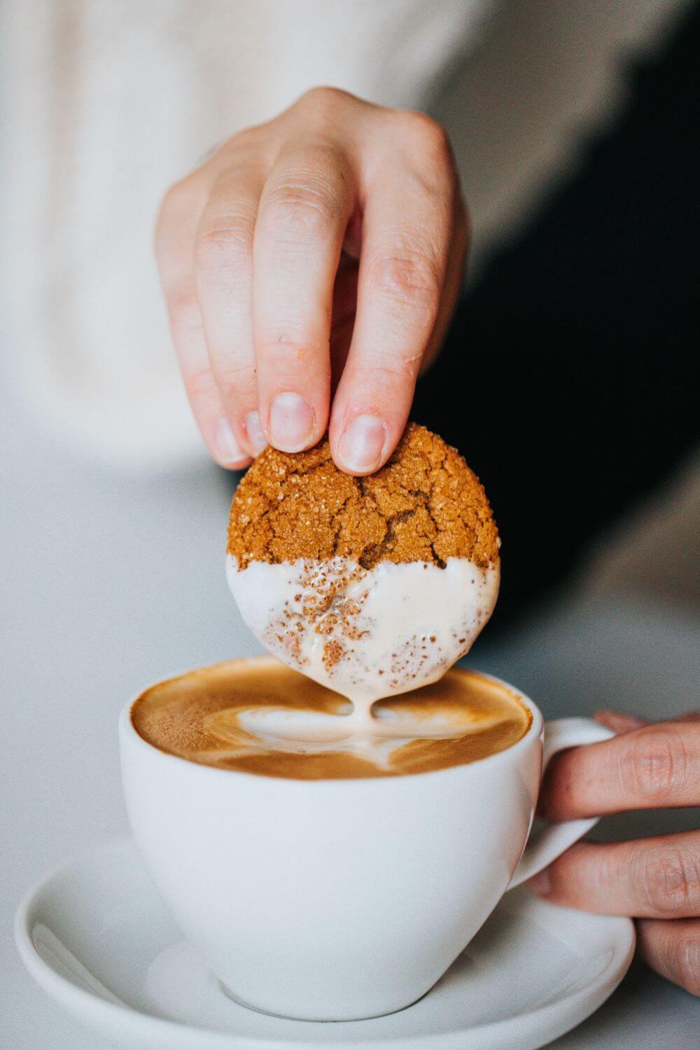 Kaffee in Porzellantasse mit Keks aus Süßigkeiten Einzelportionen